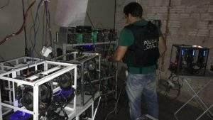 (Policial observando equipamentos de mineração de criptomoedas. Imagem: Reprodução/Polícia Civil)