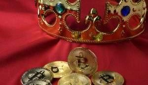 Moedas físicas de Bitcoin ao lado de uma coroa (Foto: Shutterstock)