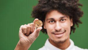 homem segurando uma moeda física de bitcoin