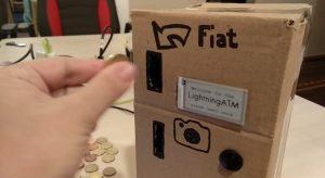 Usuário depositando uma moeda no caixa eletrônico de papelão (Imagem: Reprodução/Twitter)