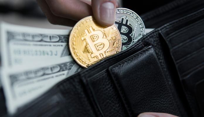 Carteira com duas moedas de bitcoin e notas de dólar